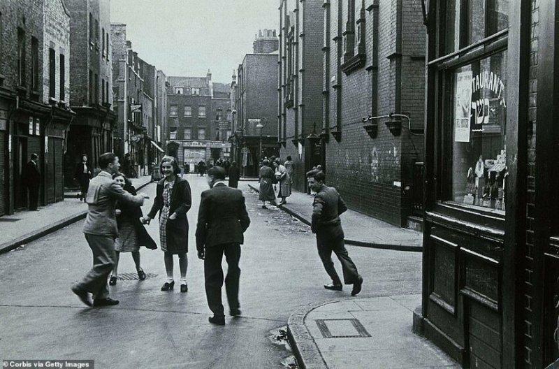 Люди играют на улице в одном из трущобных районов Уайтчепела, 1930-е годы