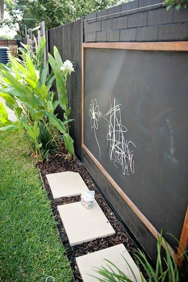 Если вы приладите к забору доску для рисования мелом - дети будут довольны, а вам не придется регулярно стирать их художественное творчество с дорожек и стен дома.