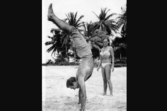 """Бонд... Джеймс Бонд: Шон Коннери пытается произвести впечатление на Урсулу Андресс, делая стойку на руках. Фотография была сделана на съемочной площадке «Доктора Ноу"""" 20 век, звезды, знаменитости, знаменитости в молодости, известные, известные люди, известные люди в молодости, старые фотографии"""