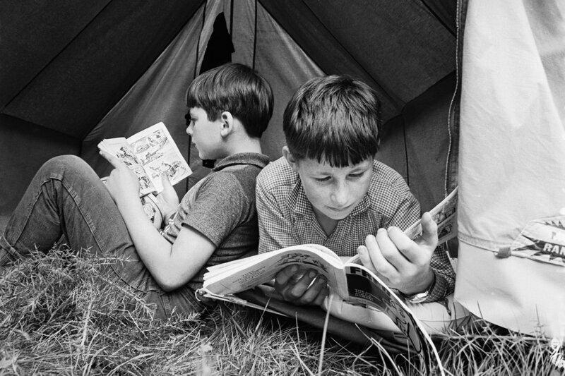 Мальчики читают комиксы в своей палатке в летнем лагере, организованном Национальной ассоциацией одаренных детей в 1967 г.