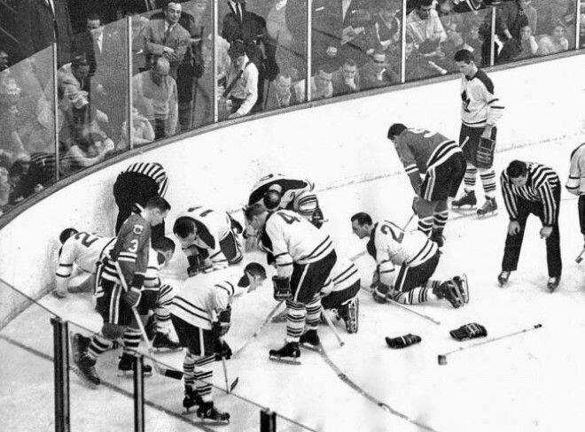 11. Игроки Toronto Maple Leafs и Chicago Black Hawks ищут выпавшую дорогую контактную линзу Джека Эванса
