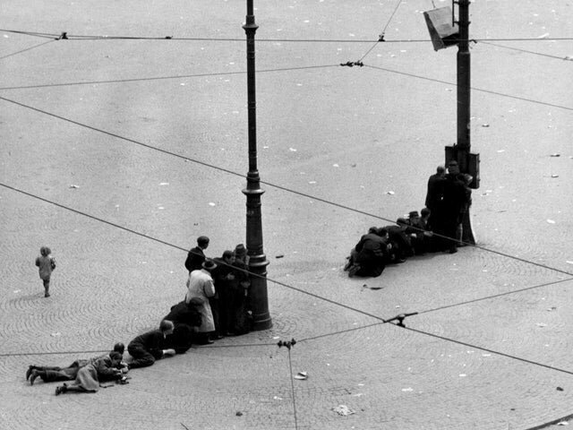3. Жители Амстердама прячутся за фонарными столбами на площади Дам во время обстрела немецкими войсками, 1945