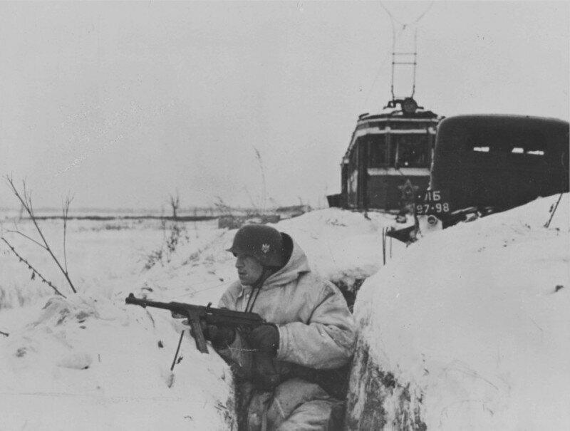 Немецкий автоматчик с МР-38/40 в окопе под Ленинградом у брошенного советского автомобиля ГАЗ-М1 и трамвайного вагона. 1941