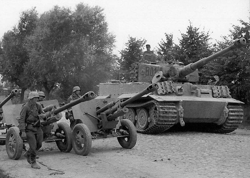 Танк «Тигр» (Pz.Kpfw. VI Ausf. E Tiger) панцер-гренадерской дивизии «Великая Германия», проезжает рядом с советскими 76-мм орудиями ЗИС-3 по улице городка Вилкавишкис. Литва, осень 1944 года