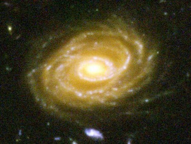 Это - галактика UDF 423. Она находится в миллиардах световых лет от Земли. Глядя на нее, вы смотрите на миллиарды лет в прошлое