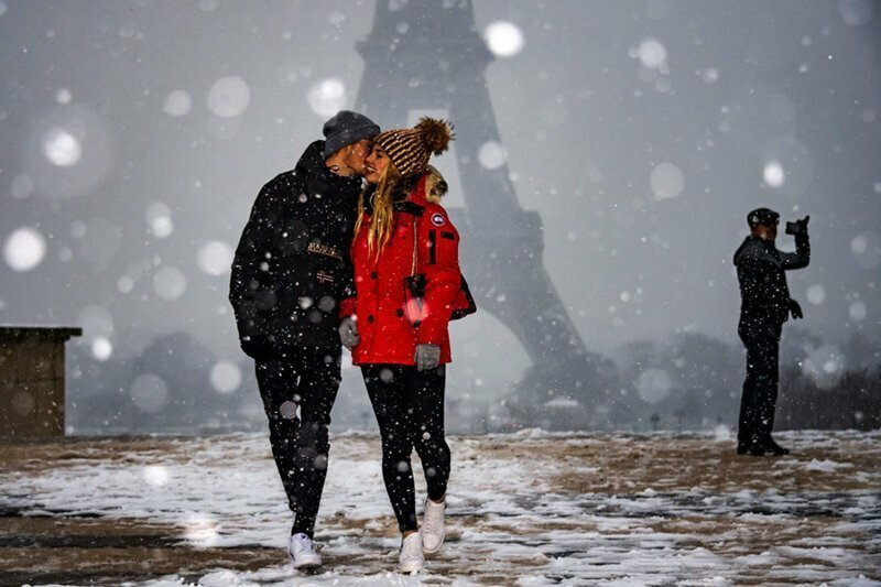 14. Пара на фоне заснеженной Эйфелевой башни в Париже