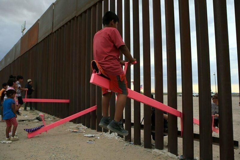 17. Дети из США и Мексики катаются на качелях, установленных на границе стран
