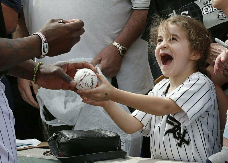 28. Маленькая фанатка получает автограф от Джоэла Букера — бейсболиста клуба White Sox