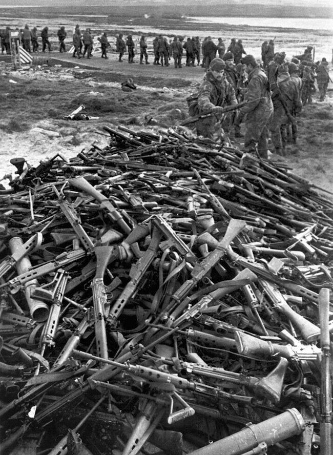 Аргентинские солдаты сдают свое оружие королевским морским пехотинцам после сдачи Фолклендских островов