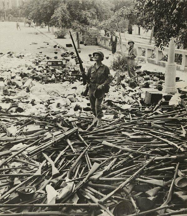 Солдат военной полиции США, стоящий на куче итальянских винтовок и шлемов после захвата Палермо, Сицилия, июль 1943 года