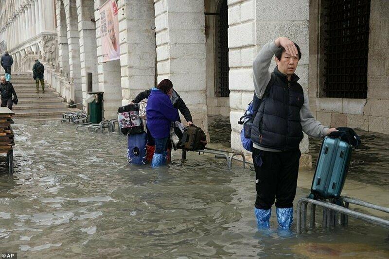 Туристы с чемоданами пробираются через водные заторы