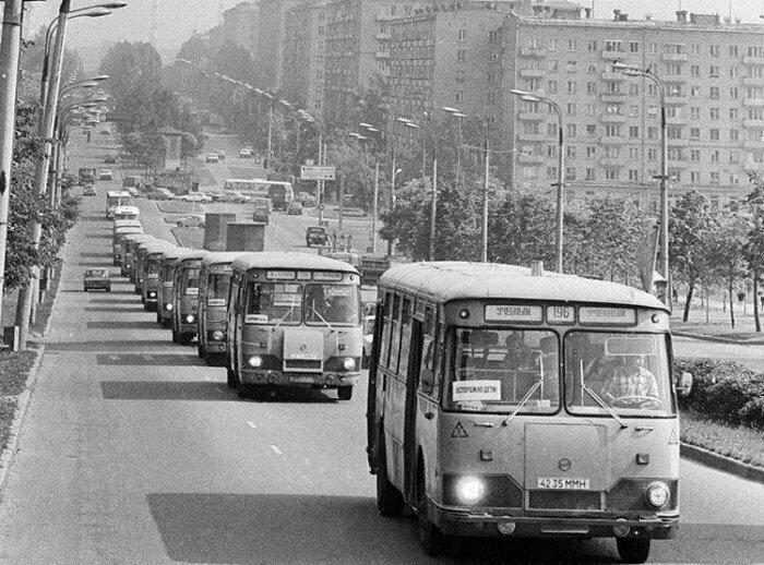 Колона автобусов ЛиАЗ везет счастливых пионеров в пионерский лагерь. Москва, 1982 год