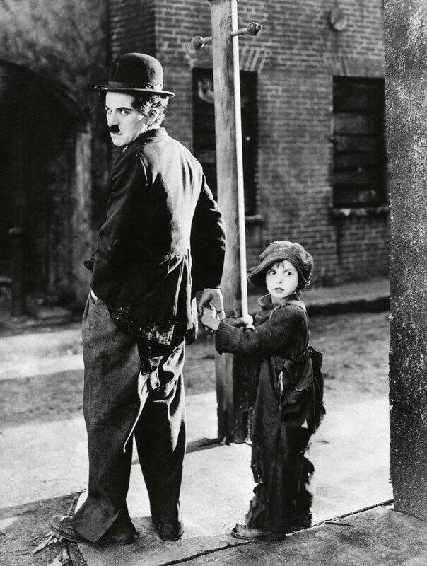 Чарли Чаплин во время съемок своего первого полнометражного фильма «Малыш» с Джеки Куганом, одним из первых детских актеров в истории кино. США, 1921