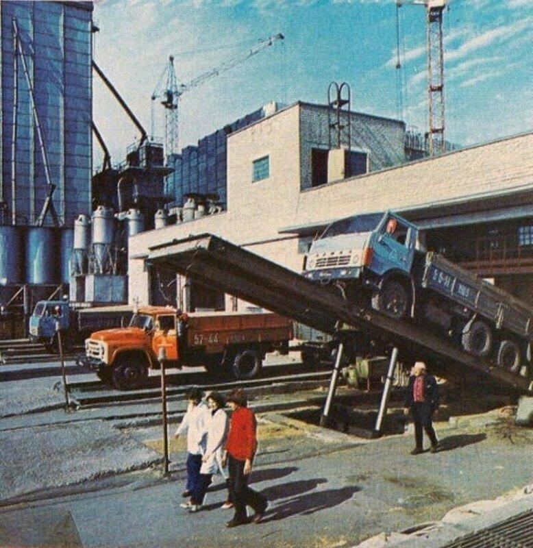 Процесс разгрузки бортовых грузовиков с зерном на территории одного из крупных элеваторов. СССР, 1980-е
