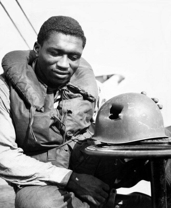 Американский солдат со своим шлемом, пробитым осколком во время операции «Драгун»; высадка союзников на юге Франции, 1944 г