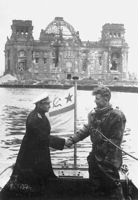 Контр-адмирал советского флота Крылов благодарит водолаза за расчистку реки Шпрее в центре Берлина  на фоне Рейхстага, в 1945 год
