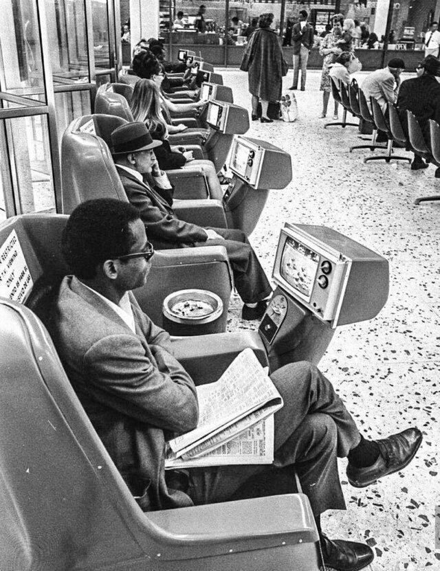 В ожидании транспорта на автобусной станции Greyhound в Лос-Анджелесе пассажиры смотрят телевизоры, включающиеся с помощью монеток, 1969 год