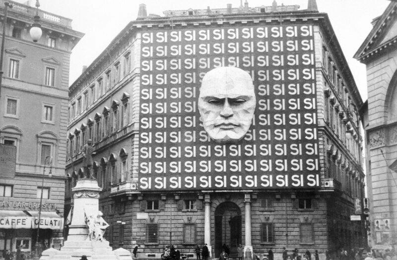 Пропагандистский плакат с портретом Бенито Муссолини и сотней слов Si на фасаде палаццо Браски,где размещался офис фашистской партии,апрель 1934 года.В настоящее время размещается Музей Рима.