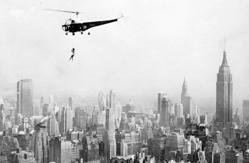 Гимнастка выполняет трюки, свисая с вертолёта над небоскрёбом Манхэттена,27 апреля 1951 года
