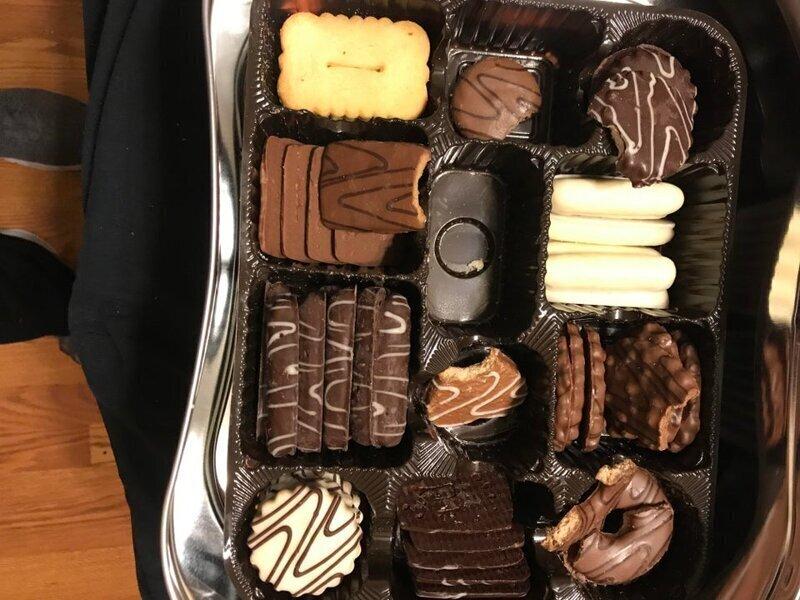 Брат надкусывает печенье, и кладёт его обратно в коробку