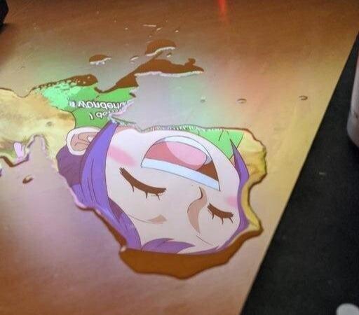 Вода вылилась на стол, и в ней отразилось изображение с компьютера