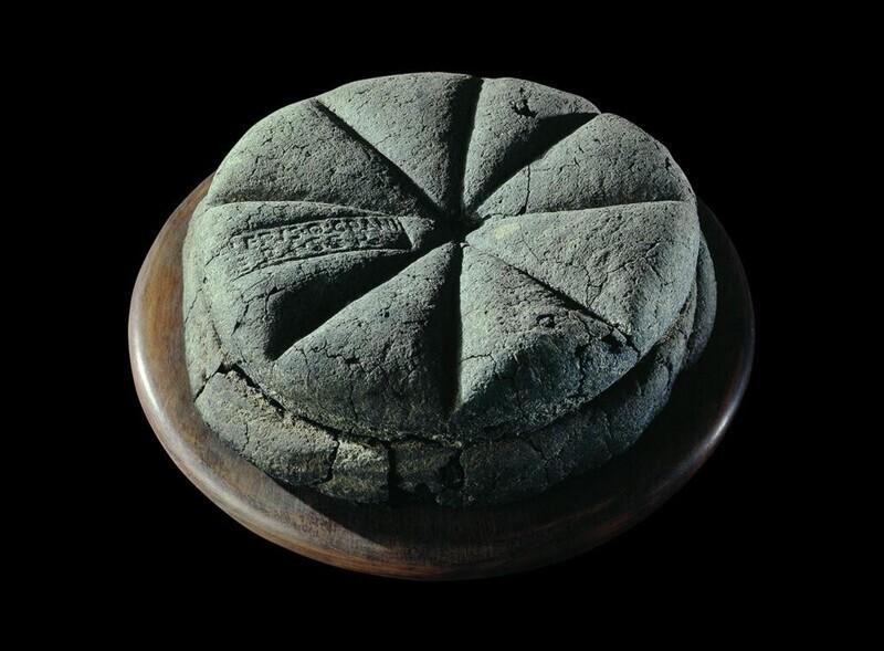"""Обугленный хлеб с печатью """"Собственность Целера, раба Q. Granius Verus"""". Геркуланум, 79 г. н.э."""