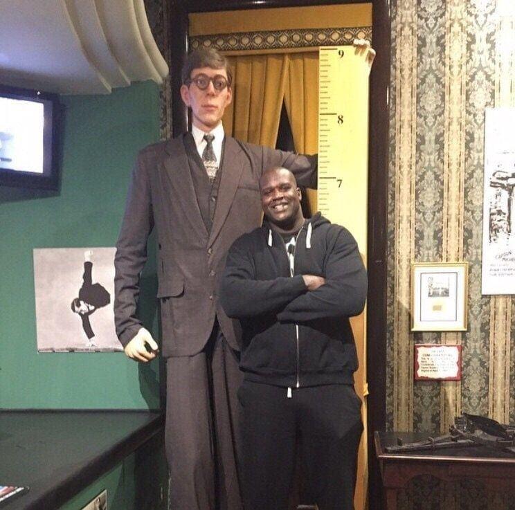 Баскетболист Шакил О'Нил (рост 2,16 метра) рядом со статуей самого высокого человека в истории