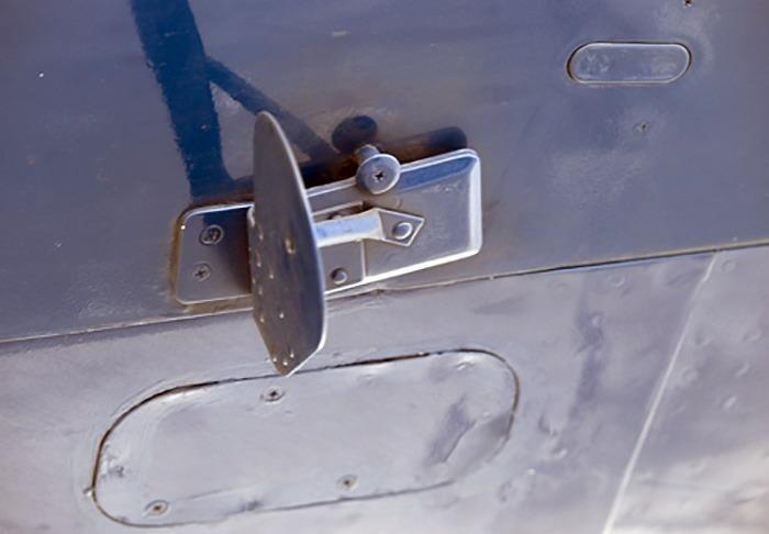 Это простая «защелка». На стоянке легкая пружинка держит ее в открытом положении (как на фото) и она не мешает открывать люк. А при полете, сильный поток воздуха давит на ее лопасть и поворачивает, тем самым закрывая люк.