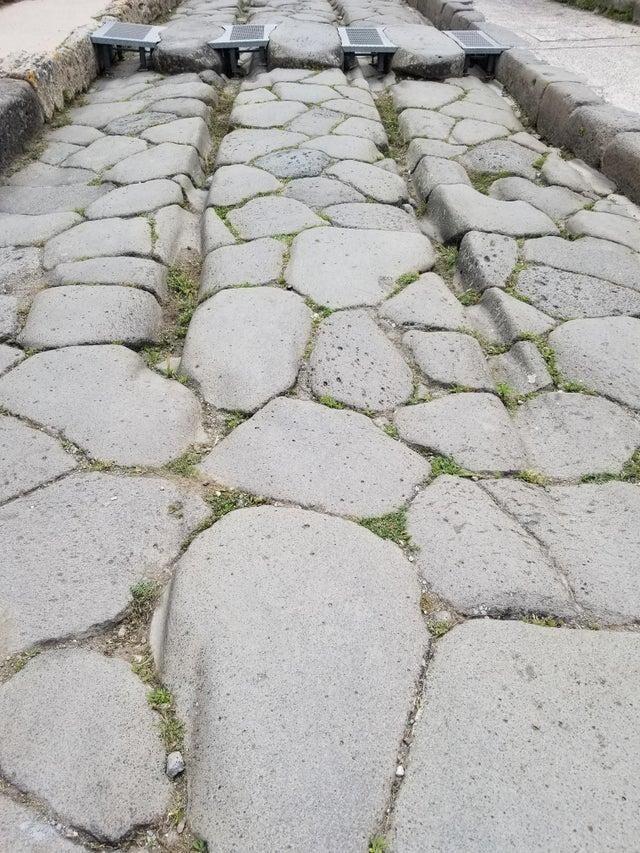 Эти следы были выбиты колесами повозок на каменной дороге в Помпеях тысячи лет назад.