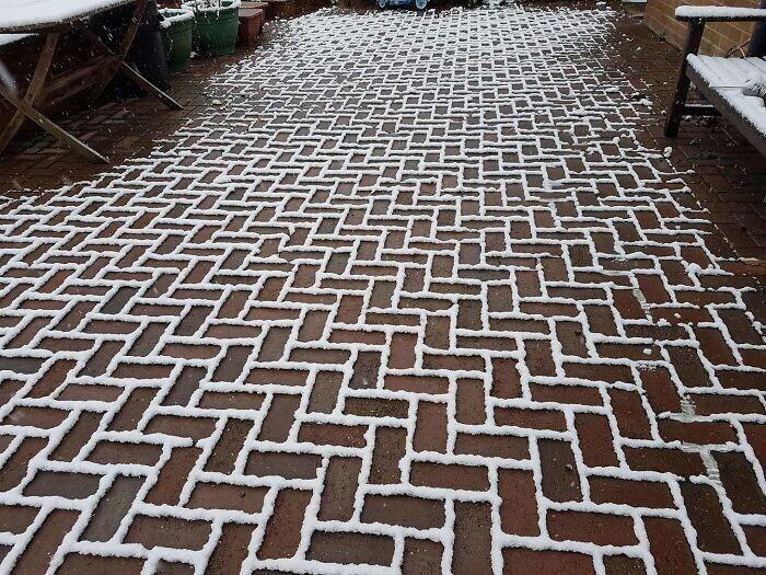 Снег лег затейливым узором - ровно по швам между плитками