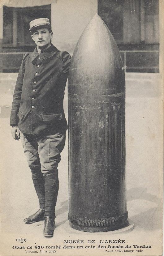 Французский солдат стоит рядом с неразорвавшимся 420-мм снарядом, упавшим на Верден. Март 1916 года. Он весил 2100 фунтов (952 килограмма)