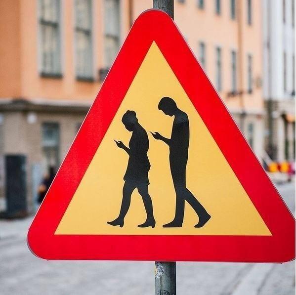 Дорожный знак предупреждает водителей, что они могут столкнуться с пешеходами, которые глубоко поглощены своими смартфонами, в Стокгольме, Швеция