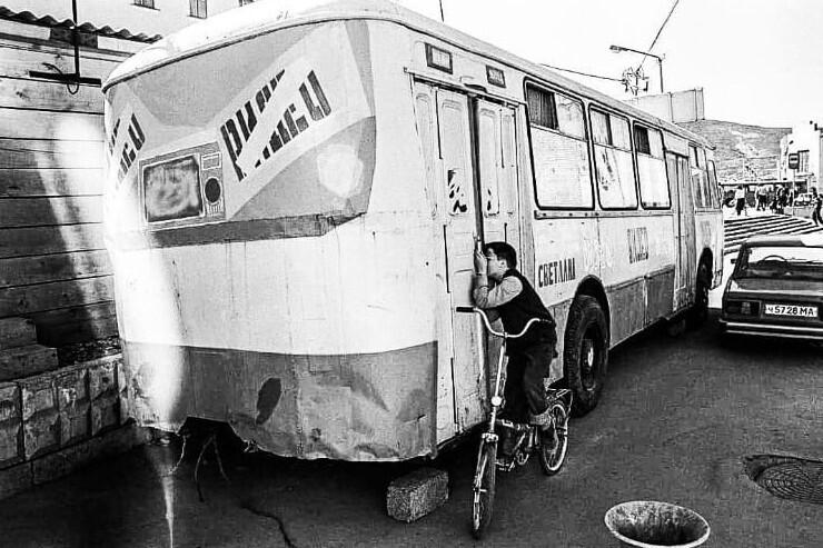 19. Мальчик подсматривает за показом фильма в видеосалоне, который находится в автобусе, Магадан, 1994 год