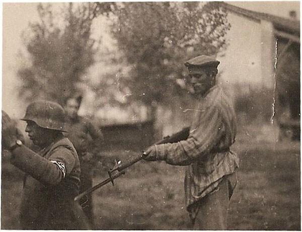 38. Освобожденный еврей держит нацистского охранника под прицелом