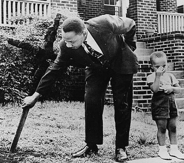 12. Мартин Лютер Кинг-младший убирает сгоревший крест со своего двора в 1960 году. Рядом его сын