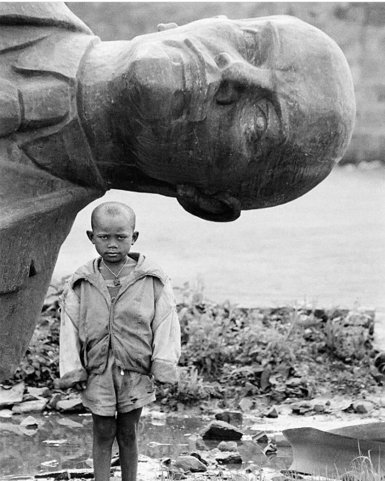 Мальчик на фоне снесенной статуи Ленина, Эфиопия, 1991 г.