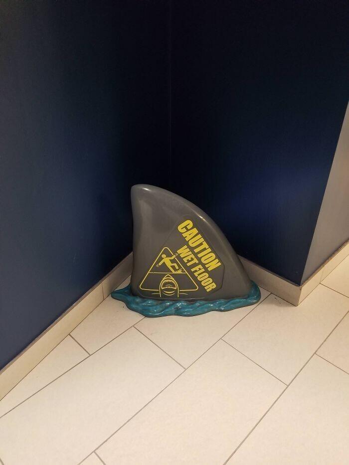 Табличка, предупреждающая о том, что пол мокрый, в виде акульего плавника