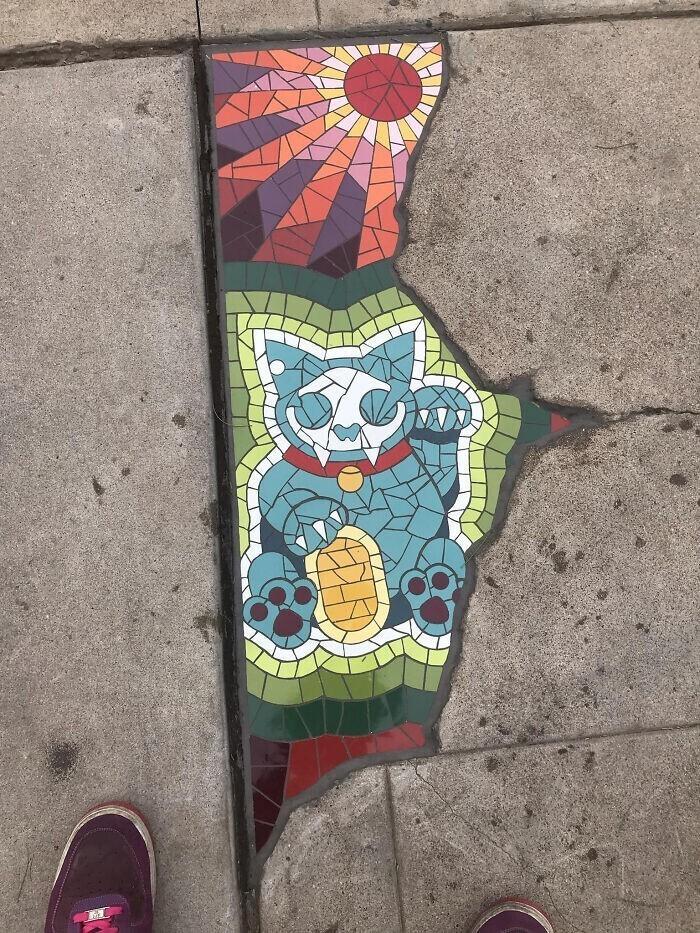 Трещину в асфальте закрыли мозаичным котиком